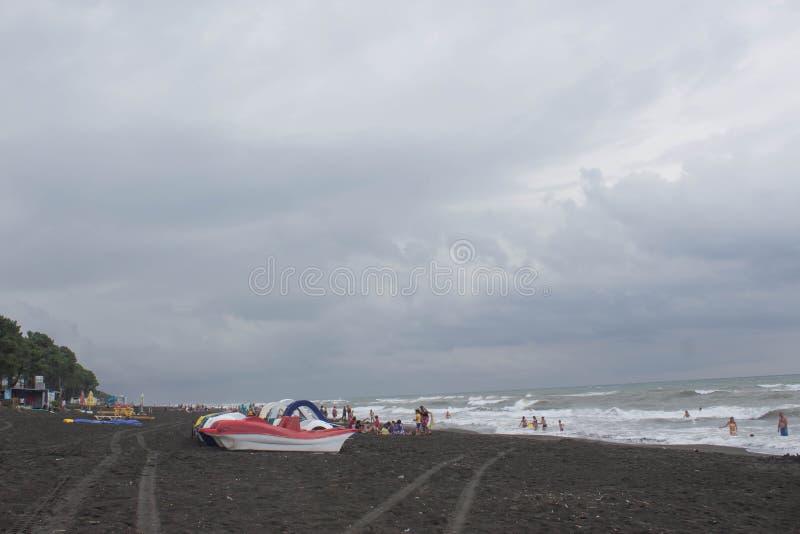 A série colorida de pedalo estacionou na praia, nublado, nuvens, ondas foto de stock