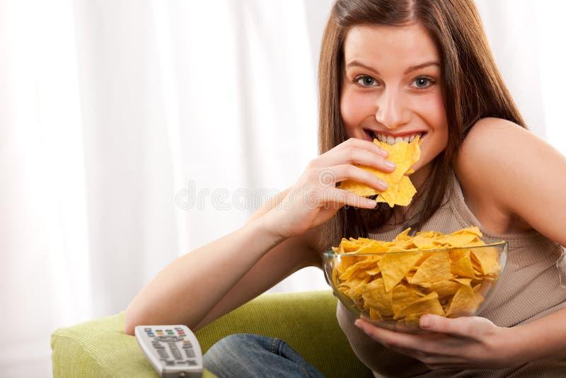 Série d'étudiant - jeune femme mangeant des pommes chips images stock
