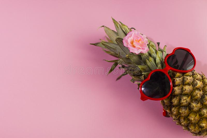 Série d'ananas avec des lunettes de soleil sur le fond bleu et rose jaune photographie stock libre de droits