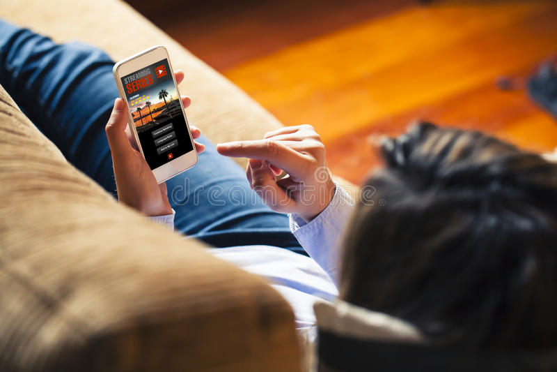 Série télévisée de observation de femme dans un téléphone portable APP tandis que repos à la maison photographie stock libre de droits
