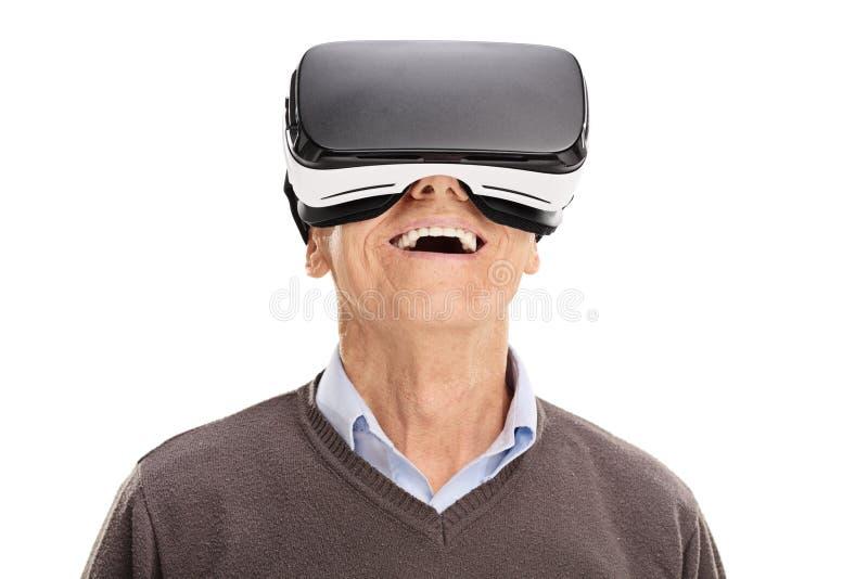 Sênior alegre que usa uns auriculares de VR foto de stock