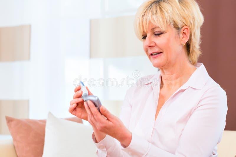 Sênior com diabetes usando o analisador da glicemia fotografia de stock