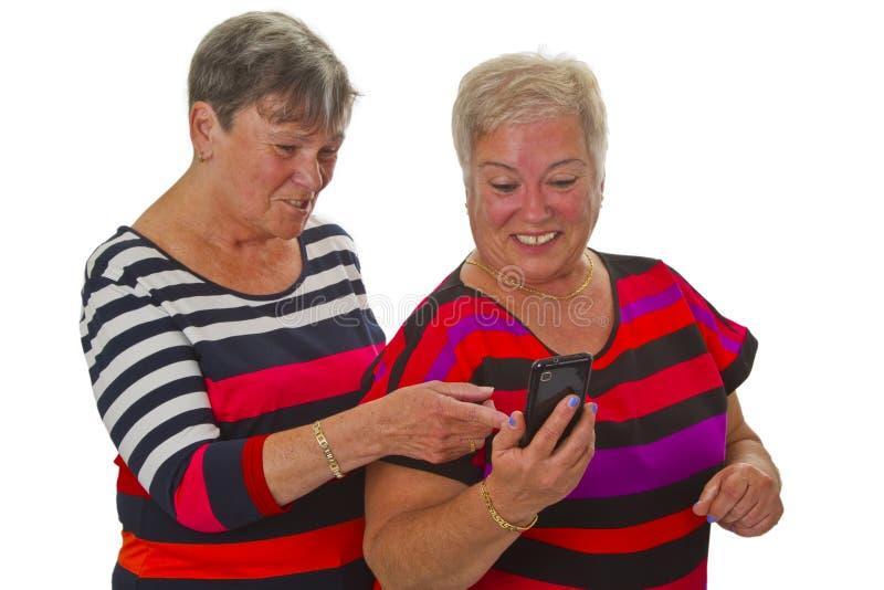 Sênior dois fêmea com telemóvel fotos de stock royalty free