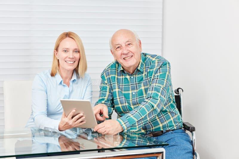 Sênior e jovem mulher curiosos com tabuleta imagem de stock