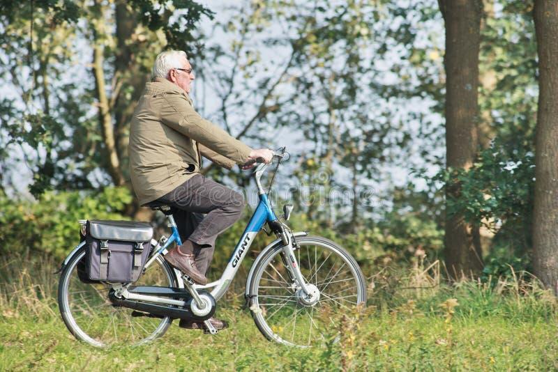 Sênior em uma e-bicicleta gigante, Tilburg, Países Baixos fotografia de stock royalty free