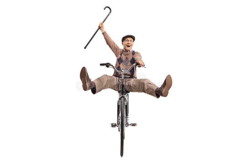 Sênior extático com um bastão que monta uma bicicleta imagens de stock