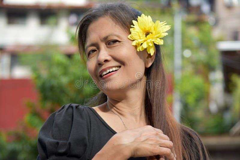 Sênior fêmea asiático feliz com uma margarida fotografia de stock royalty free