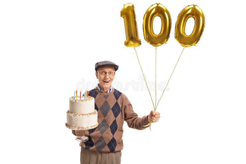 Sênior feliz com um bolo de aniversário e um balão do número cem imagens de stock