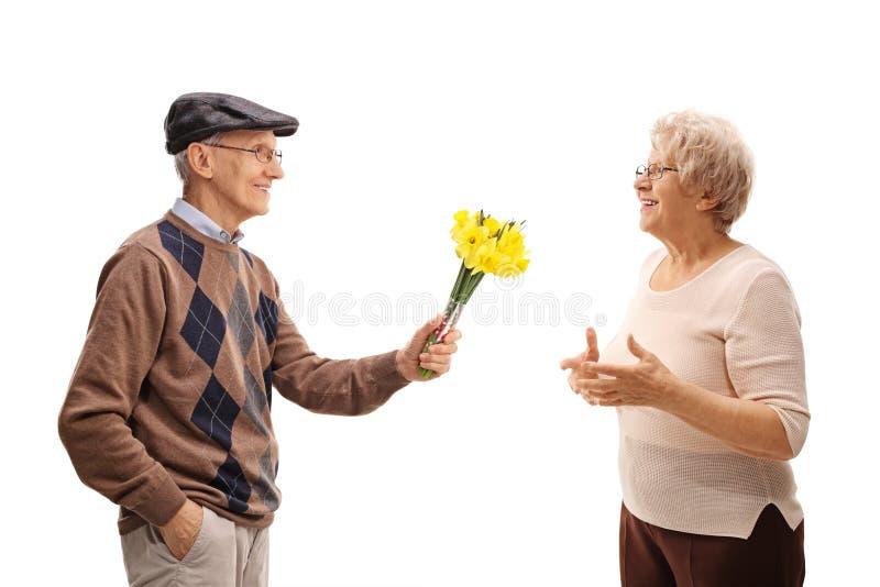 Sênior pensativo que dá flores a uma senhora foto de stock