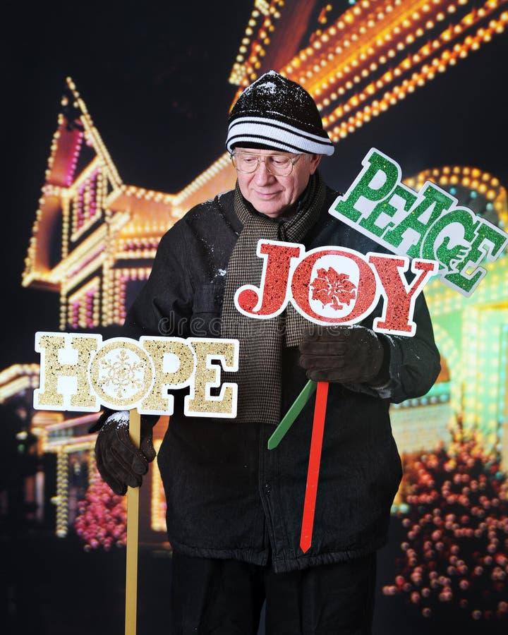 Sênior que coloca sinais da jarda do Natal fotos de stock royalty free