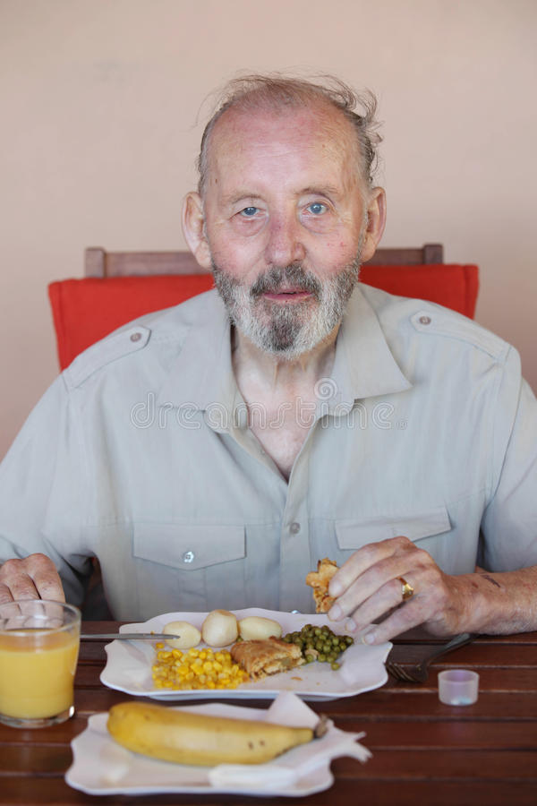 Sênior que come a refeição saudável na casa dos cuidados domiciliários foto de stock royalty free