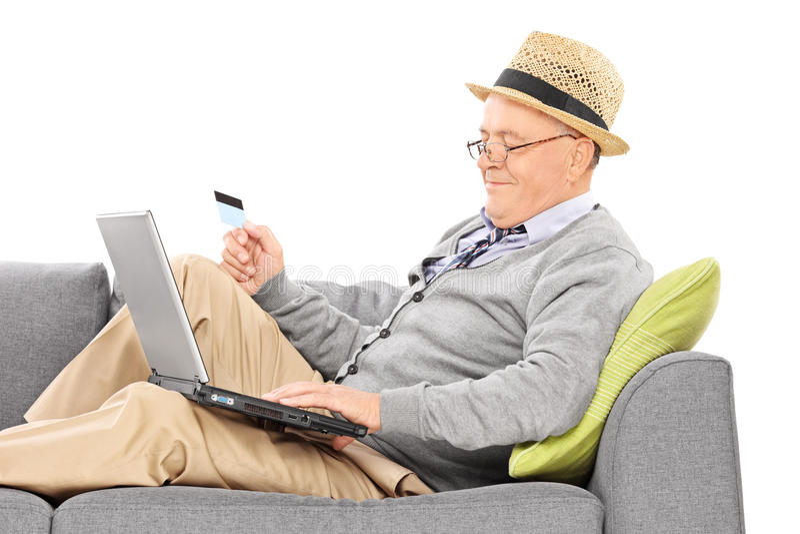 Sênior que guarda um cartão de crédito e que trabalha no portátil fotos de stock royalty free