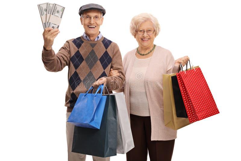 Sêniores alegres com os pacotes de dinheiro e de sacos de compras imagens de stock royalty free