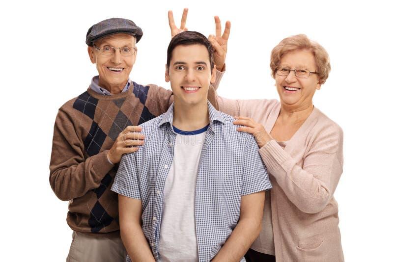 Sêniores alegres que pranking um homem novo com orelhas do coelho fotografia de stock royalty free