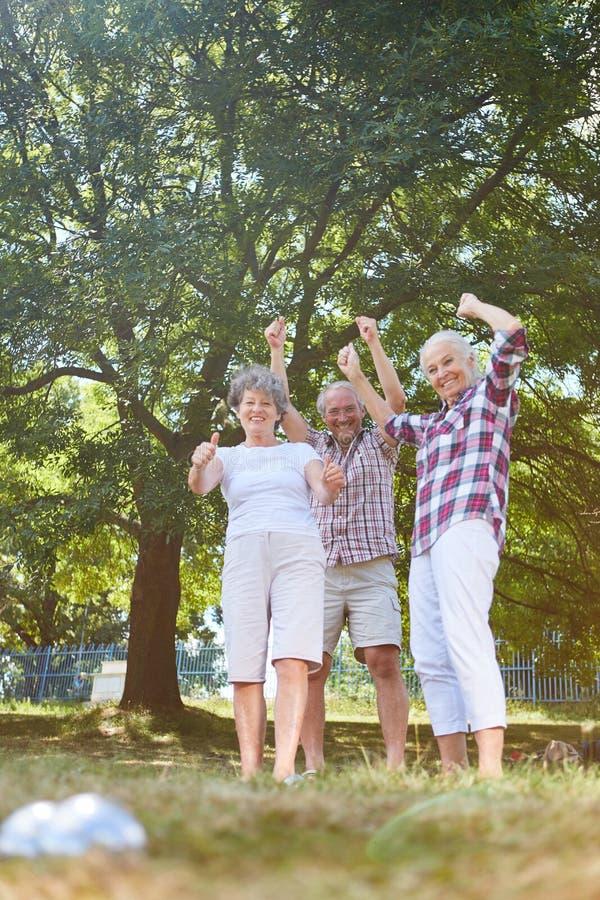 Sêniores ativos que cheering ao jogar boules foto de stock