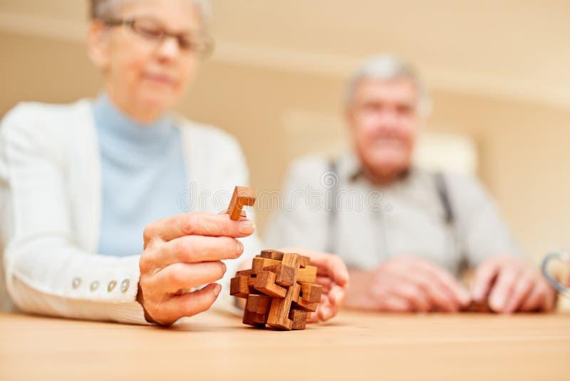 Sêniores com jogo da demência com um enigma de madeira imagem de stock royalty free