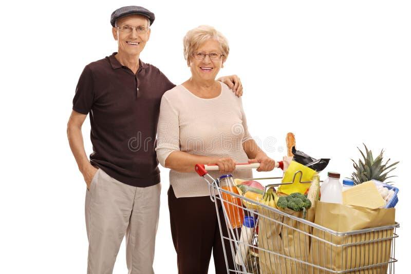 Sêniores com um carrinho de compras completo dos mantimentos foto de stock