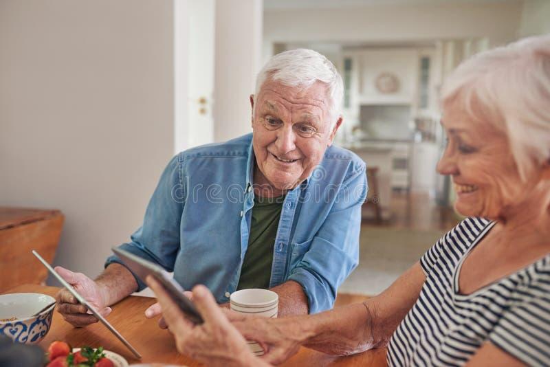 Sêniores de sorriso que usam tabuletas digitais junto sobre o café da manhã imagem de stock royalty free