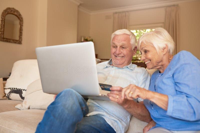 Sêniores felizes que compram em linha de seu sofá da sala de visitas foto de stock
