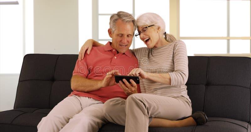 Sêniores modernos que sentam-se em vídeos de observação do sofá no smartphone foto de stock royalty free