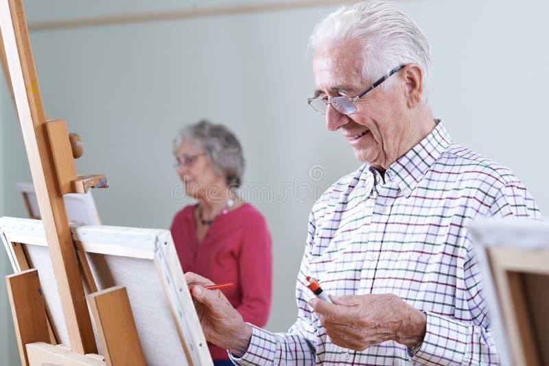 Sêniores que atendem à classe da pintura junto imagem de stock