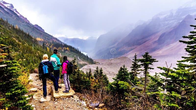 Sêniores que caminham nas moraine de Victoria Glacier parque nacional em Lake Louise, Banff fotos de stock