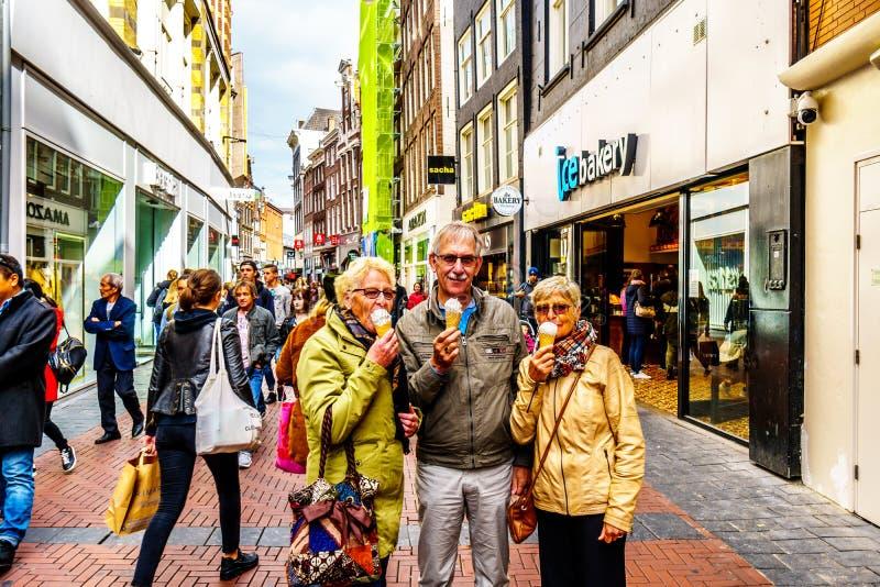 Sêniores que comem um cone de gelado na rua ocupada da compra de Niewendijk no centro histórico de Amsterdão imagens de stock royalty free