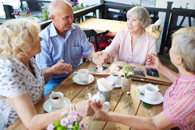 Sêniores que guardam as mãos no café imagens de stock royalty free