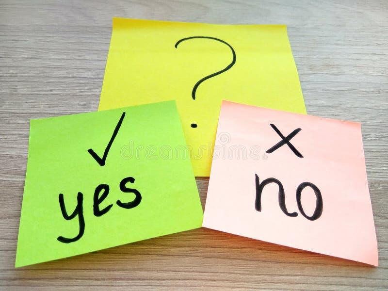 Sì o nessun messaggio di domanda sulle note appiccicose su fondo di legno Soluzione dei problemi e concetto di scelta immagini stock