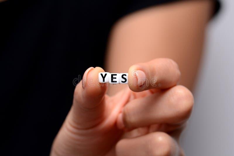SÌ parola dai blocchetti di plastica bianchi della lettera in mano della donna fotografia stock libera da diritti