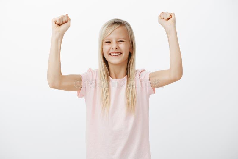 Sí, pequeño campeón lindo feliz de ganar en juego de ordenador Retrato del estudio de la muchacha adorable alegre positiva con la fotografía de archivo
