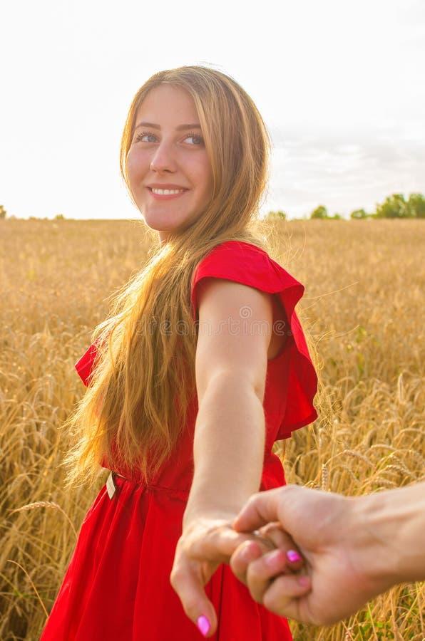 Sígame, controles románticos hermosos de la mujer joven la mano de un hombre en un campo de trigo imagen de archivo