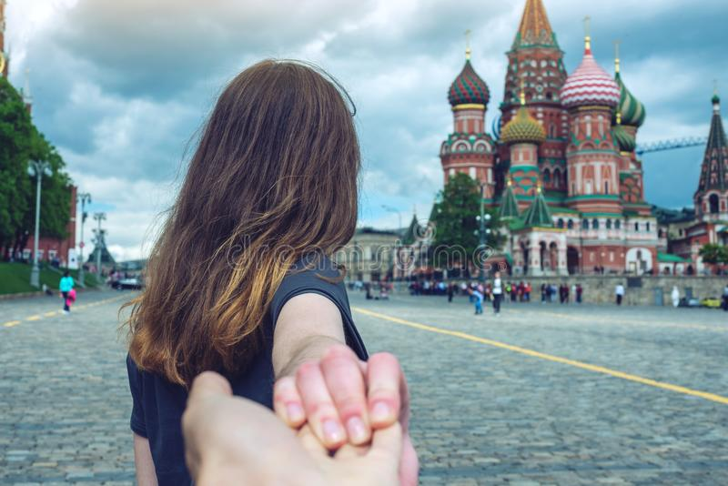 Sígame, muchacha morena atractiva que lleva a cabo la mano lleva al cuadrado rojo en Moscú Rusia imagen de archivo