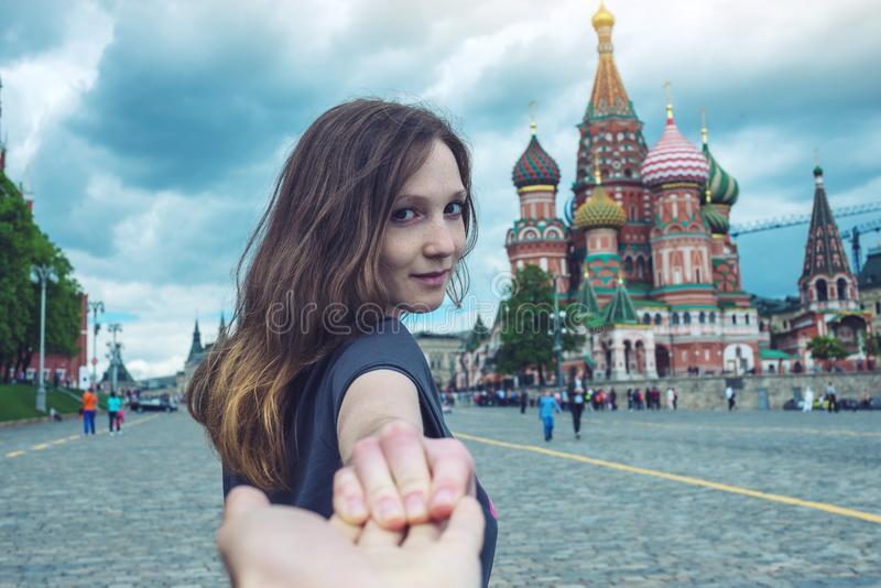 Sígame, muchacha morena atractiva que lleva a cabo la mano lleva al cuadrado rojo en Moscú Rusia imágenes de archivo libres de regalías