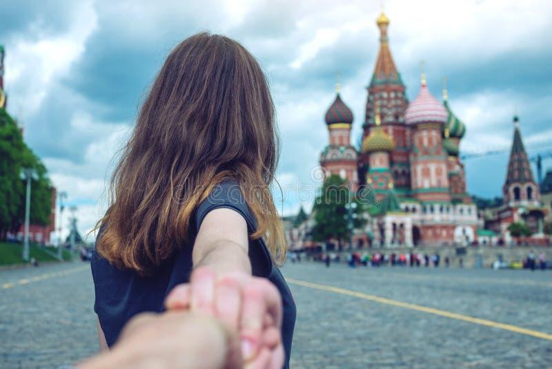 Sígame, muchacha morena atractiva que lleva a cabo la mano lleva al cuadrado rojo en Moscú Rusia fotografía de archivo libre de regalías