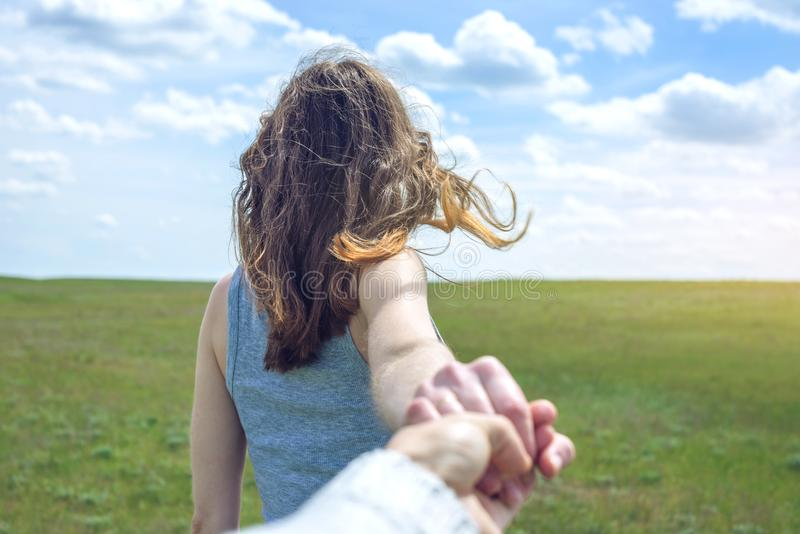 Sígame, muchacha morena atractiva que lleva a cabo la mano de las ventajas en un campo verde limpio, estepa con las nubes imagen de archivo libre de regalías