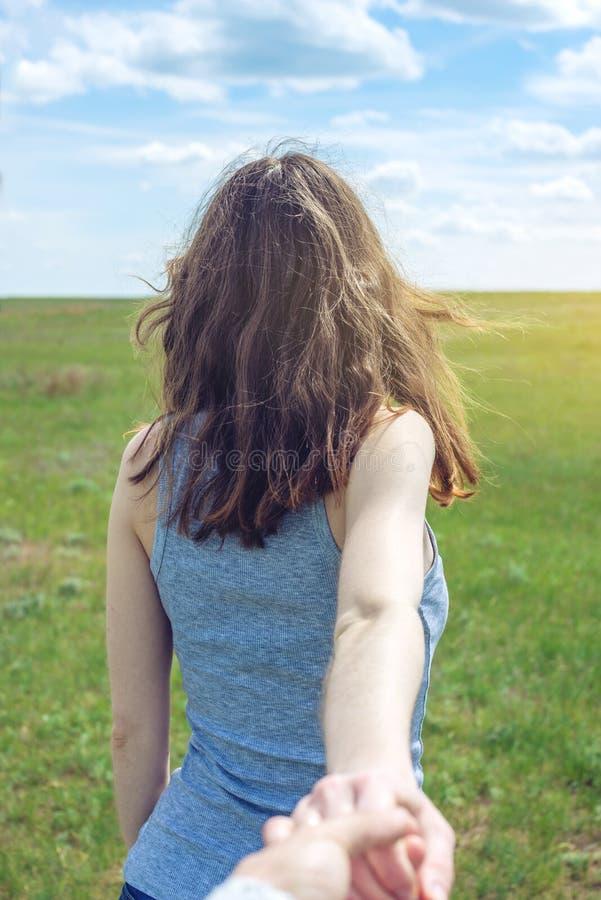 Sígame, muchacha morena atractiva que lleva a cabo la mano de las ventajas en un campo verde limpio, estepa con las nubes imágenes de archivo libres de regalías