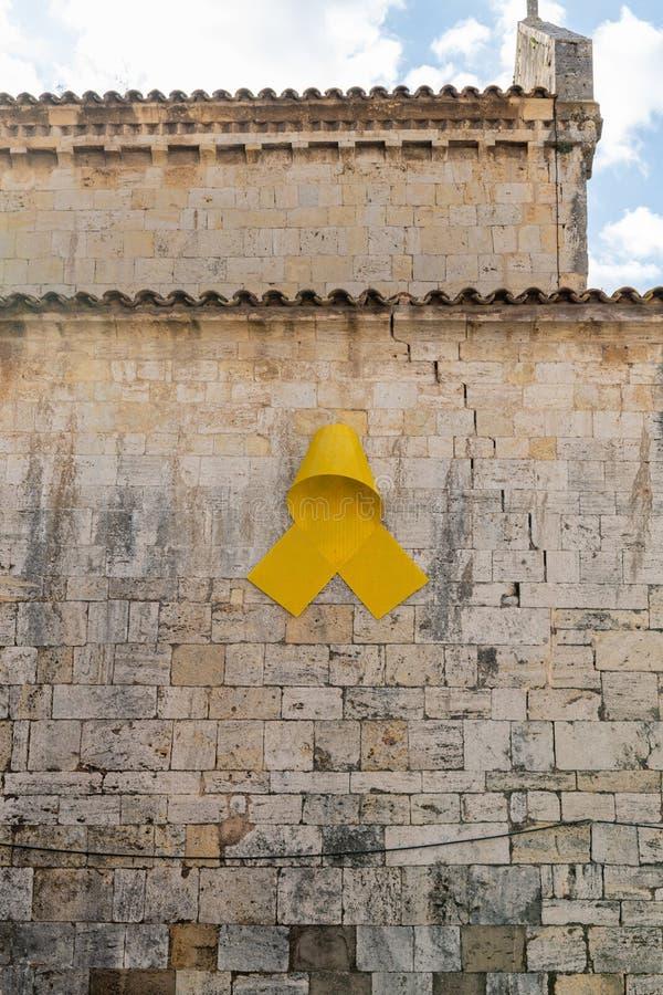 Símbolo amarillo catalán español de la cinta para la independencia en la pared de piedra vieja de una catedral foto de archivo