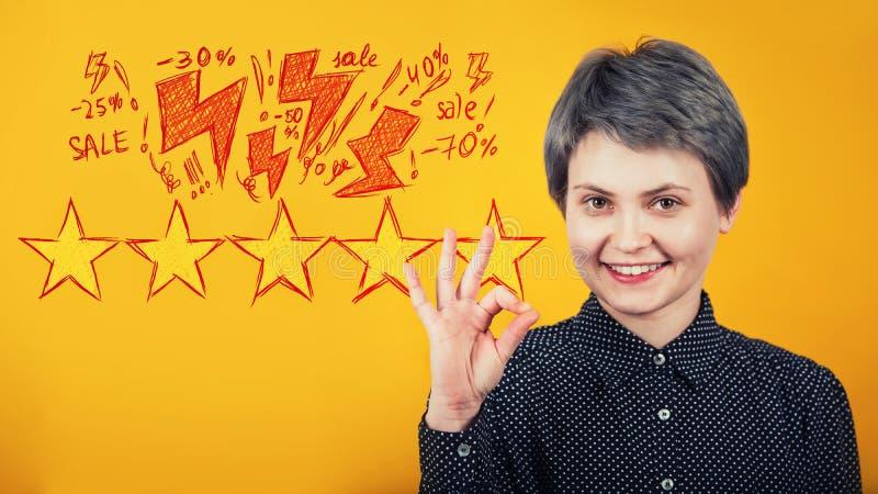 Símbolo aprovado da exibição satisfeito do moderno da mulher como a aprovação e como o gesto, suportes sobre a parede amarela Exc ilustração do vetor