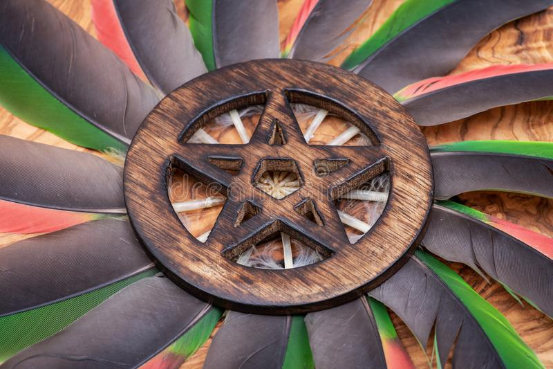 Símbolo cercado de madera del Pentagram en el medio de un círculo hecho de plumas coloridas del loro Cinco elementos fotografía de archivo