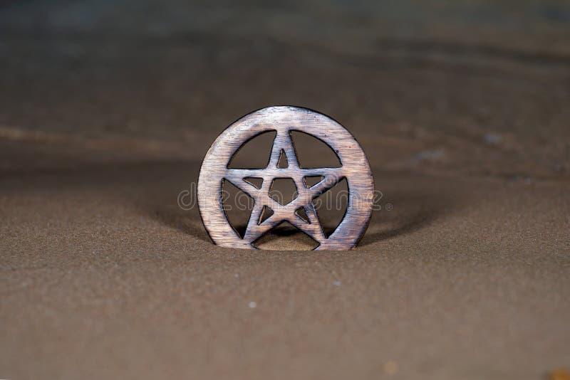 Símbolo cercado de madera del Pentagram en la playa en la salida del sol delante del lago Concepto de cinco elementos: imágenes de archivo libres de regalías