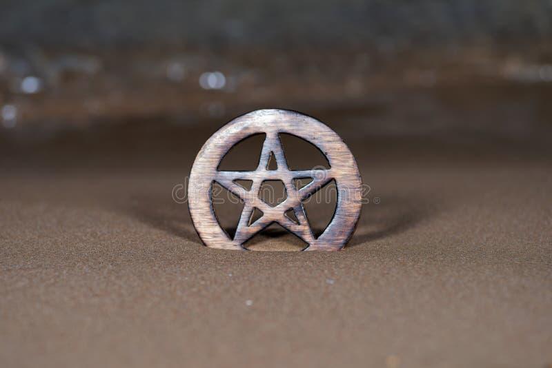 Símbolo cercado de madera del Pentagram en la playa en la salida del sol delante del lago Concepto de cinco elementos: fotos de archivo