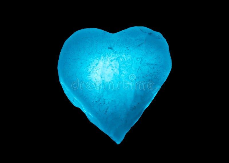 Símbolo congelado del corazón del hielo azul del primer aislado en un fondo negro imagenes de archivo