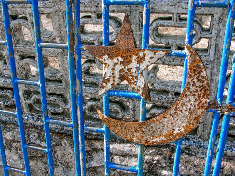 Símbolo crescente da estrela oxidada unido à porta azul de aço na entrada de uma mesquita velha foto de stock royalty free