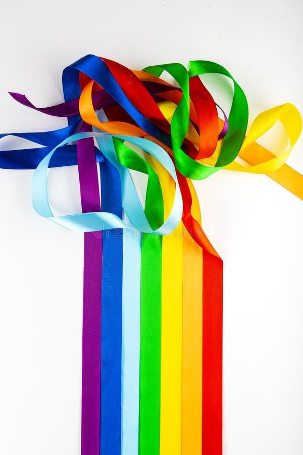 Símbolo da bandeira de LGBT feito de fitas do cetim em um fundo branco Um arco-íris de misturas das fitas um com o otro fotografia de stock