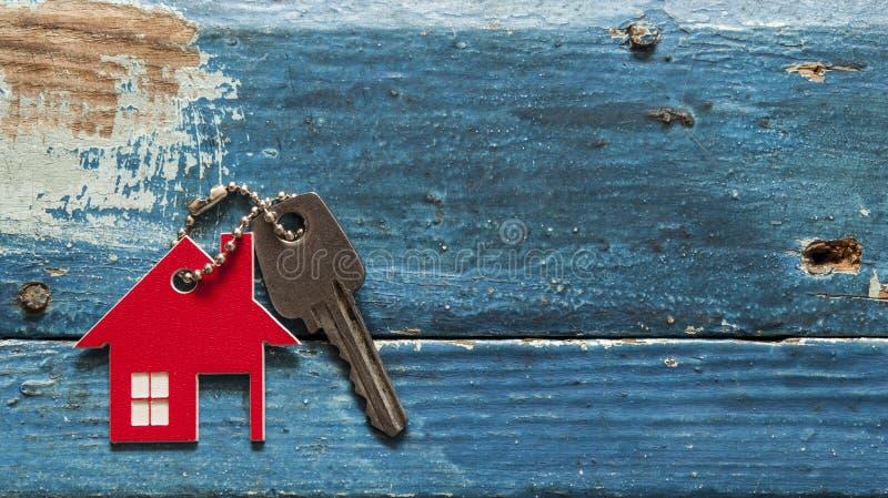 Símbolo da casa com chave de prata no fundo de madeira do vintage imagem de stock