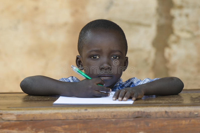 Símbolo da educação, pouco criança africana que sorri felizmente sentando-se dentro fotos de stock