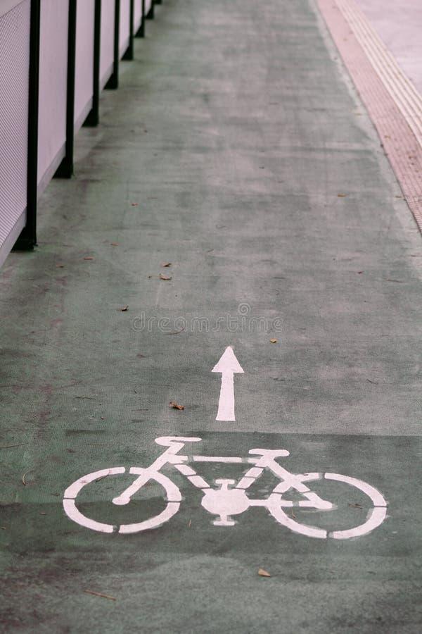 Símbolo da pista da bicicleta com uma seta do sentido na terra Sinal de estrada da fuga da bicicleta na ponte moderna para a bici foto de stock royalty free