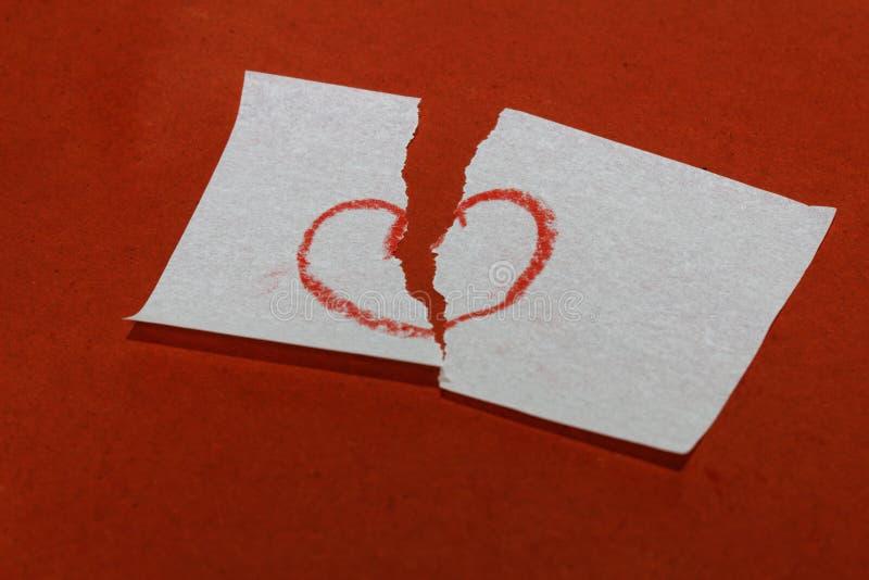 Símbolo da ruptura do coração/coração quebrado no fundo vermelho fotografia de stock