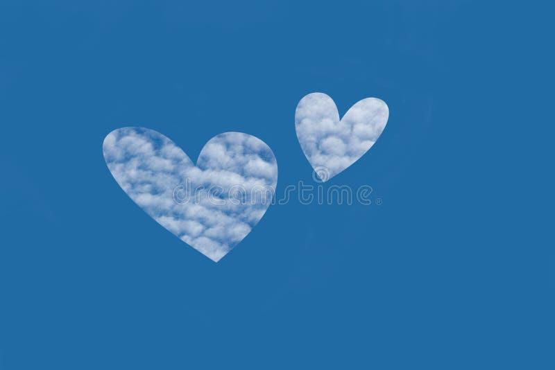 Símbolo de dois corações feitos das nuvens em um céu azul imagens de stock royalty free